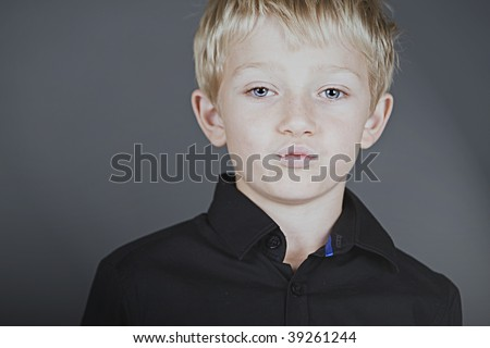 a young blonde boy with attitude pouting at the camera