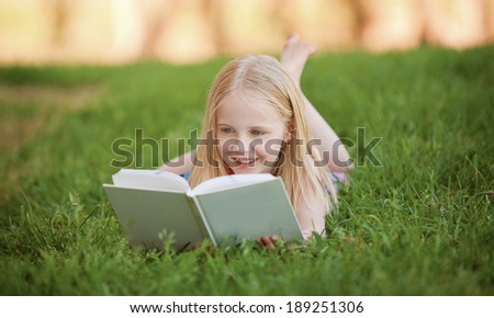 A young blonde girl is lying on the green grass outdoors reading a white book in summer - stock photo