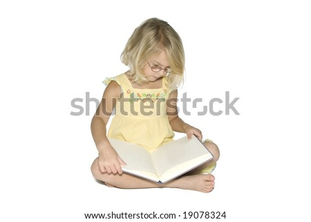 A young blonde girl sitting cross-legged while reading a textbook.  Isolated on a white background - stock photo