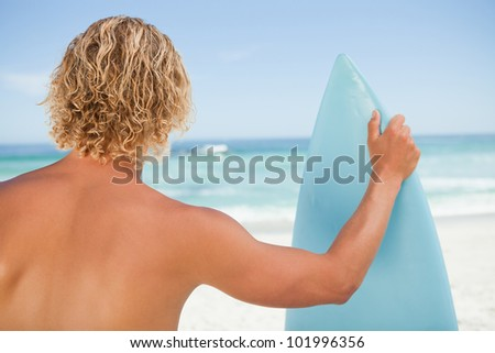 A young blonde man holding a perched surfboard while standing on the beach - stock photo