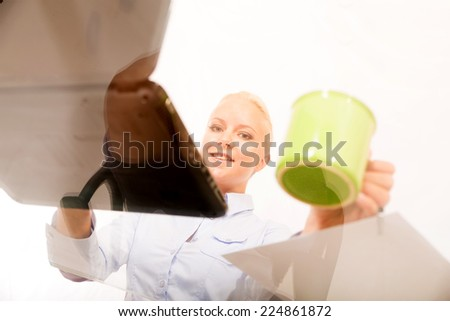 A young blonde secretary holding a cup of coffee seen from under the desk .  - stock photo