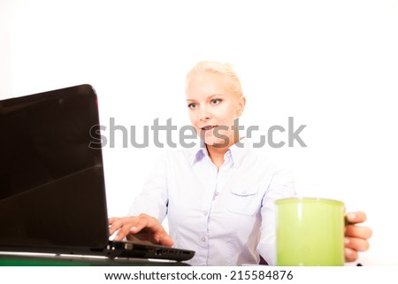 A young blonde secretary with a cup of coffee on the desk.  - stock photo