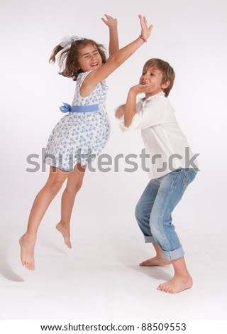 A young boy and a little girl happily playing - stock photo