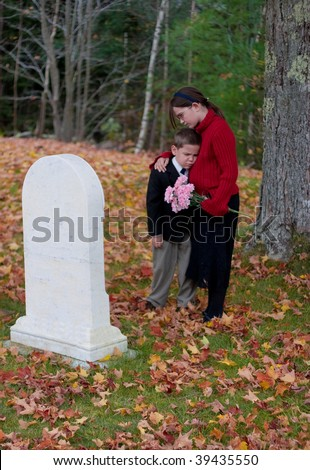 A young boy and girl grieve at a grave