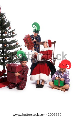 A young boy and girl sitting at the feet of Mrs Claus who is in her rocker and turned talking to an older boy behind her. Kids with presents and wearing pj's and elf hats