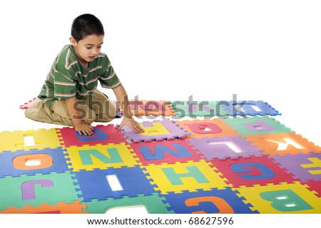 A young boy assembling a large alphabet floor puzzle.  Isolated on white. - stock photo