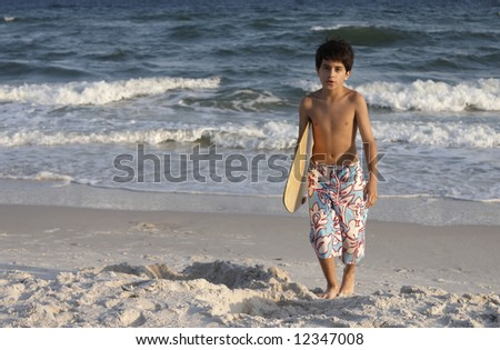 A young boy carrying a skim board. - stock photo