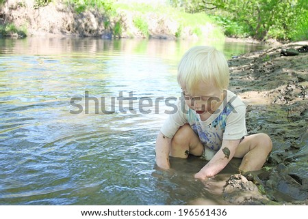a young boy child is sitting in on the beach of a river in the woods, playing in the mud on a summer day.