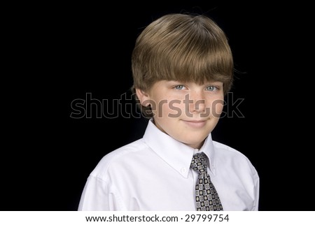 A young boy dressed in a shirt and tie has his portrait taken.  Isolated on a black backdrop. - stock photo