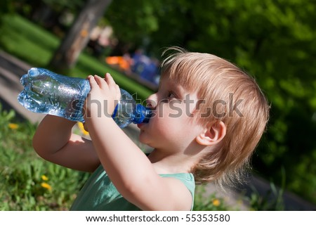 A young boy drinks from a water bottle - stock photo