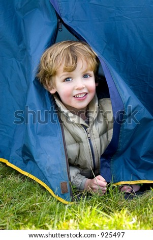 A young boy emerges from a tent on a camping trip - stock photo