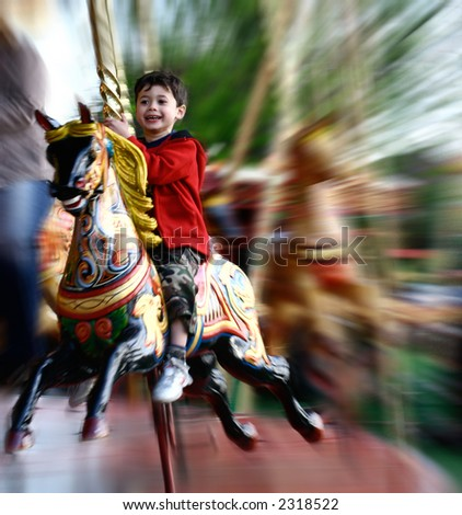 A young boy enjoying his wooden carousel ride at the steam fair.