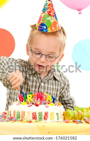 A young boy happily eats his birthday cake.