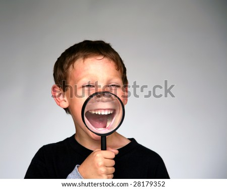 a young boy holds a magnifying glass up to his mouth for a fun and funny photo - stock photo