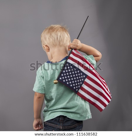 A young boy holds an American flag proudly over his shoulder.