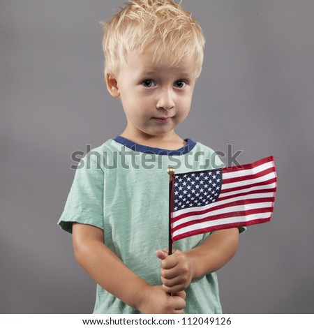 A young boy holds an American flag with a questioning look. - stock photo