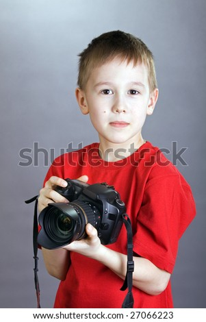 A young boy holds up a camera. - stock photo