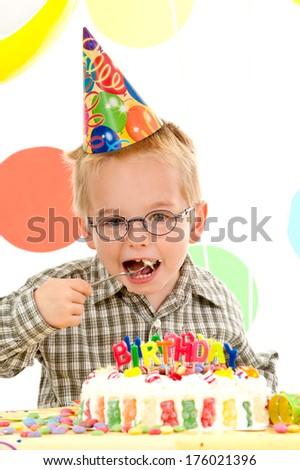 A young boy in a party hat is eating a birthday cake.