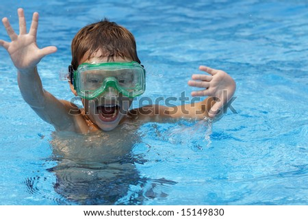 a young boy in pool with goggles on