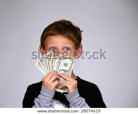 a young boy is excited by all the money he was just given - stock photo