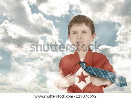 A young boy is holding his shirt open with his tie flying for a superhero bravery concept. There are clouds in the background - stock photo