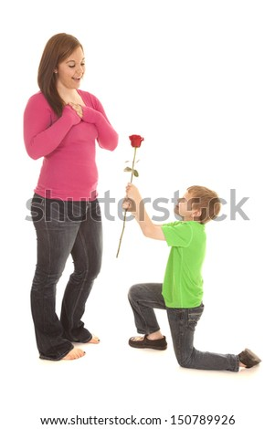 A young boy is on his knee giving a rose to a woman.