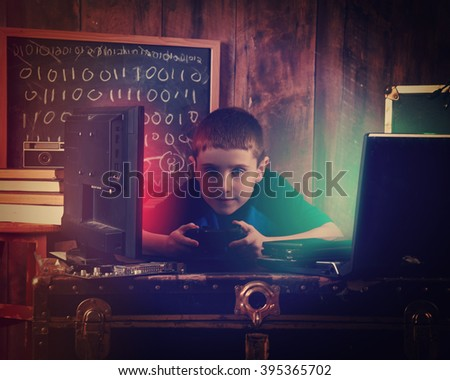 A young boy is playing with a game controller with various technology objects around him and a binary chalkboard for a gamer or entertainment concept.