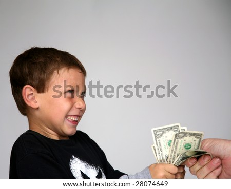 a young boy is shocked by a hand trying to take away his money - stock photo