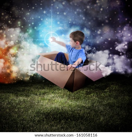 A young boy is sitting in a cardboard box and floating in the night sky reaching for a star in space. - stock photo