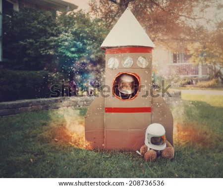 A young boy is sitting in a cardboard space rocket ship with an astronaut helmet on. He is in the front yard imagining he is in space with stars. - stock photo