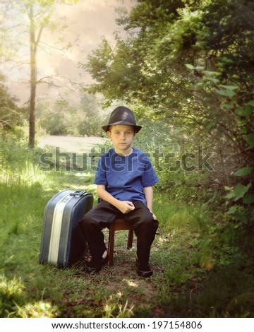 A young boy is sitting on a nature trail in the woods with a suitcase and hat. The child looks sad for a travel or vacation concept. - stock photo