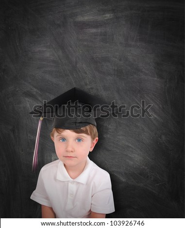 A young boy is wearing a graduation cap and tassel against a black chalk board. Add your text to the copyspace. Use it for an education or school concept. - stock photo