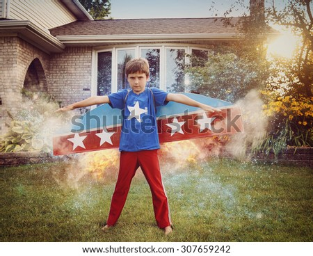 A young boy is wearing cardboard rocket wings with stars on the costume. He is in the front yard imagining he is in space with stars flying. - stock photo