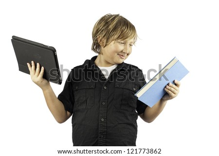 A young boy isolated on white holding a tablet pc and a book. Shows how times have changed. - stock photo