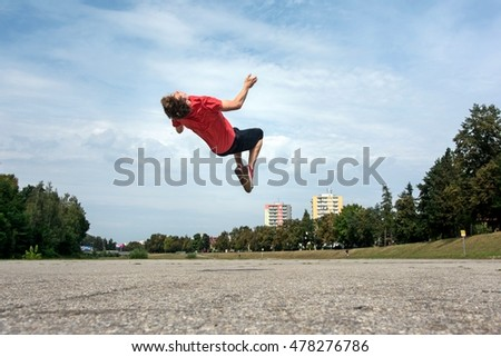 A young boy leaping somersault on the street