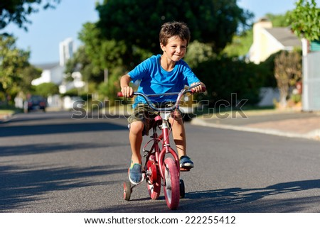 A young boy learning how to ride a bicycle on the street - stock photo