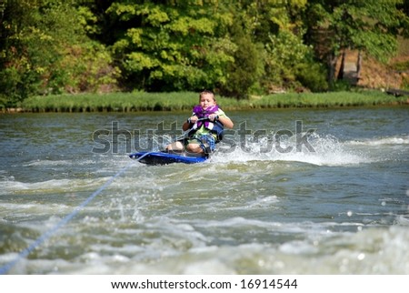 A young boy learning to knee-board on a lake in summer. - stock photo