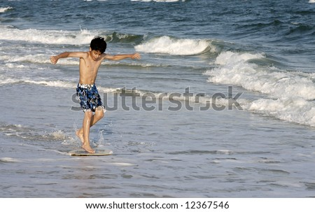 A young boy on a skimboard. - stock photo