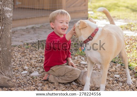 A young boy pets a dog while smiling. - stock photo