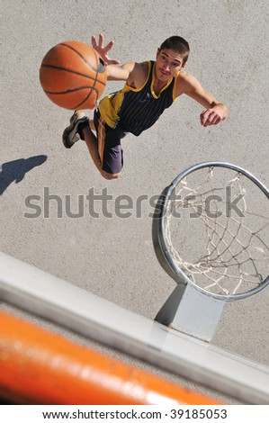a young boy playing basketball outdoor on street with long shadows and bird view perspective - stock photo