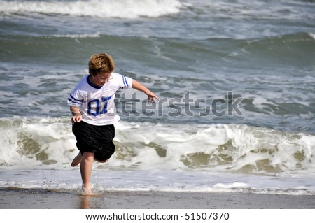 A young boy playing on the beach - stock photo