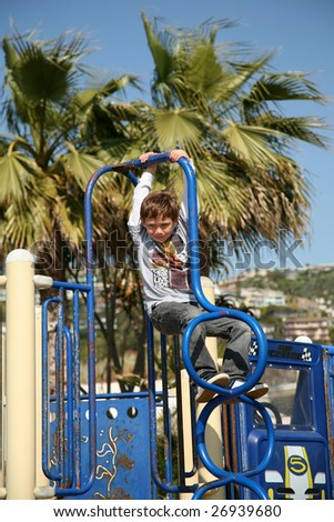 """a young boy plays on a """"Jungle Gym"""" outside on a playground in a park - stock photo"""