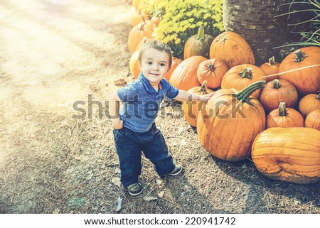 A young boy proudly poses with his hand resting on a pumpkin he has picked out at a farm during the autumn season.  Filtered for a retro, vintage look.  - stock photo