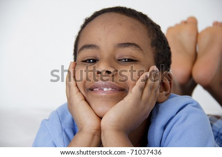 A young boy resting comfortably with his face resting on his hands - stock photo
