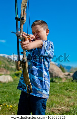 A young boy shooting a bow and arrows in the mountains.
