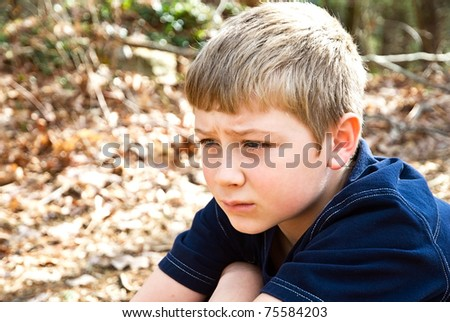 A young boy sitting outdoors, maybe he's thinking, not feeling well, or lost, the expression could relate to many emotions. - stock photo