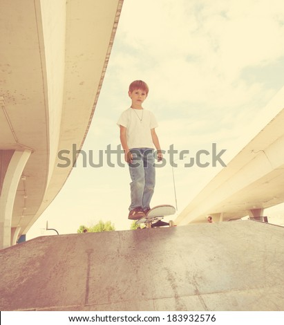 a young boy skateboarding in an urban setting done with a retro vintage instagram filter - stock photo