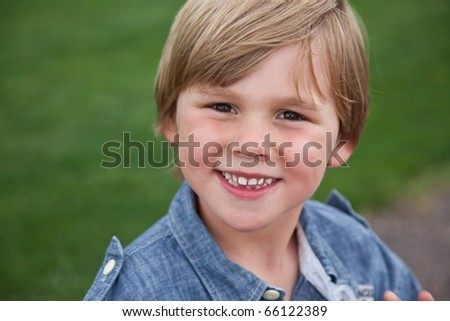 A young boy smiling in the park. - stock photo