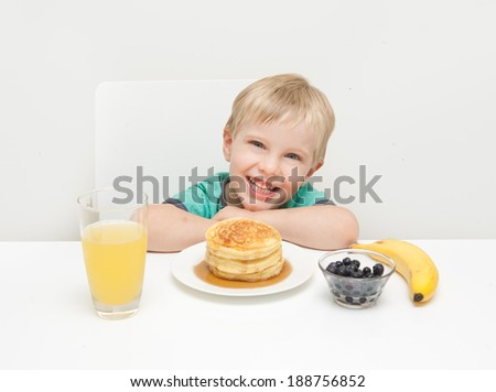A young boy smiling with his breakfast of pancakes, berries, banana and juice taken against a white background. - stock photo