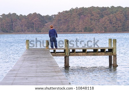 A young boy standing on a pier. - stock photo